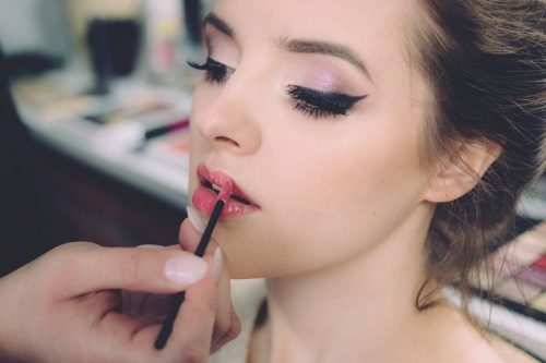 Makeup artist applying lip liner