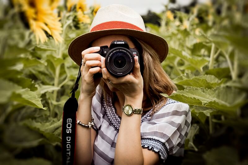 Girl taking photograph using a DSLR camera