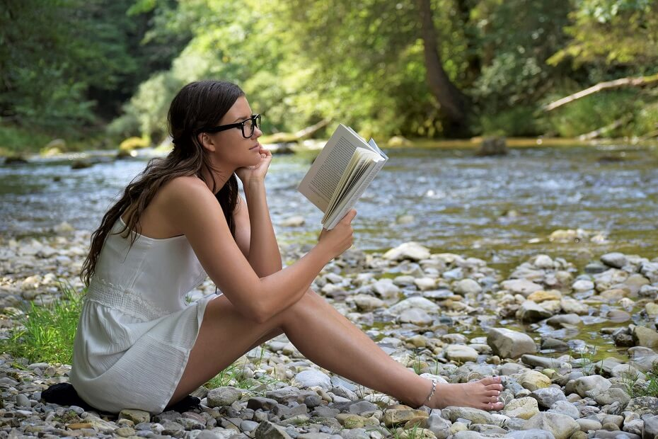 Girl reading book near a rivulet