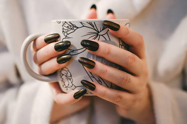 Women with Black polished nails holding cup