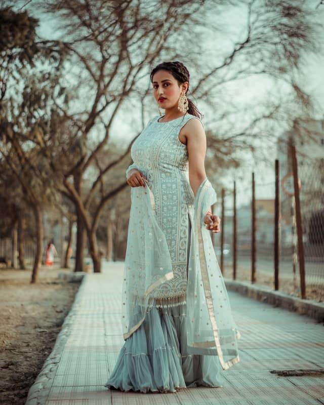 A woman wearing white elegant yet simple Salwar Kameez