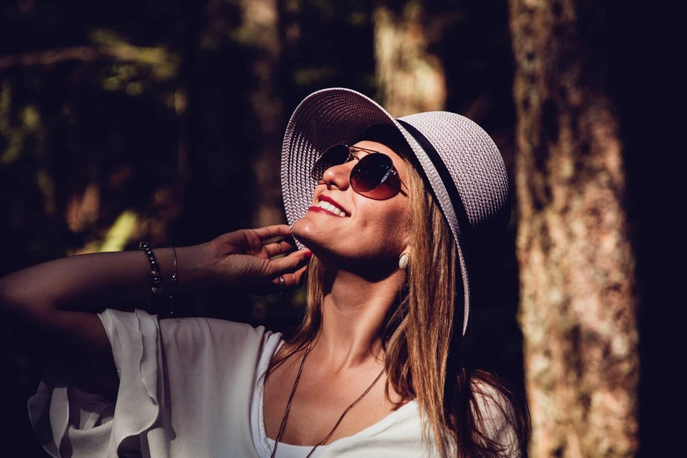 A confident woman wearing sunglasses looking at the sky