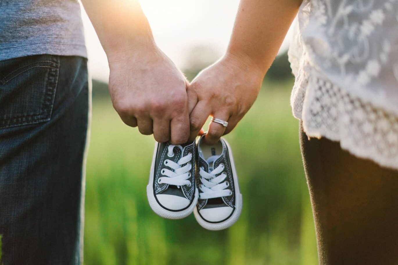 Couple holding kid's shoes in their hands