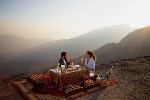 A couple enjoying the picnic on a hill