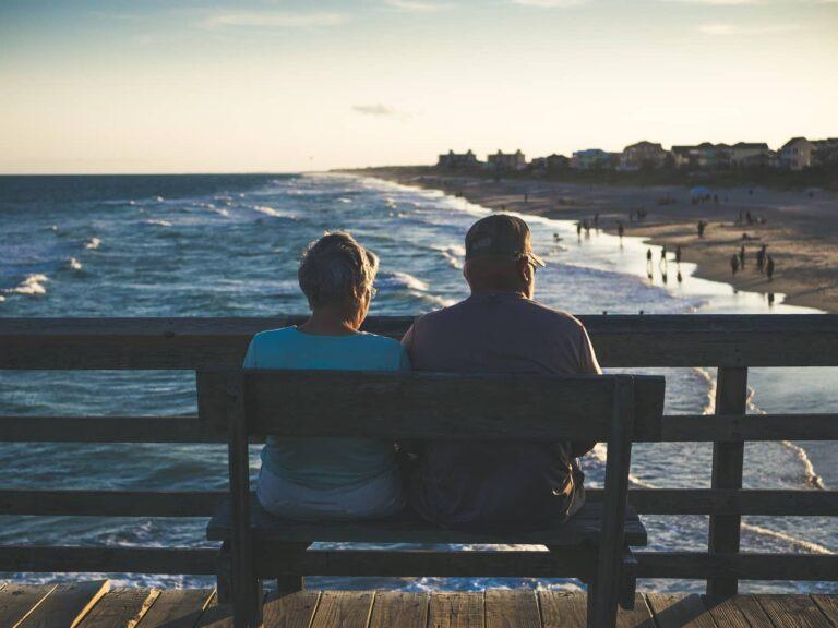 A senior couple relaxing on a bench near beach