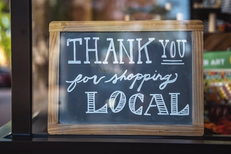 A writing board thanking customers for shopping local in a store