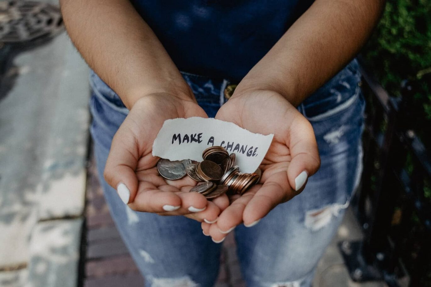 A woman holding money on her hands with a text 'Make a Change' on paper