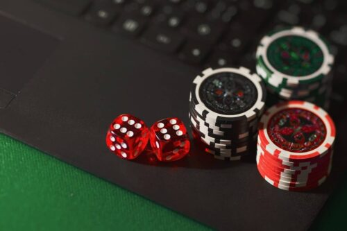 Casino chips and Dice are placed on a Laptop's keyboard