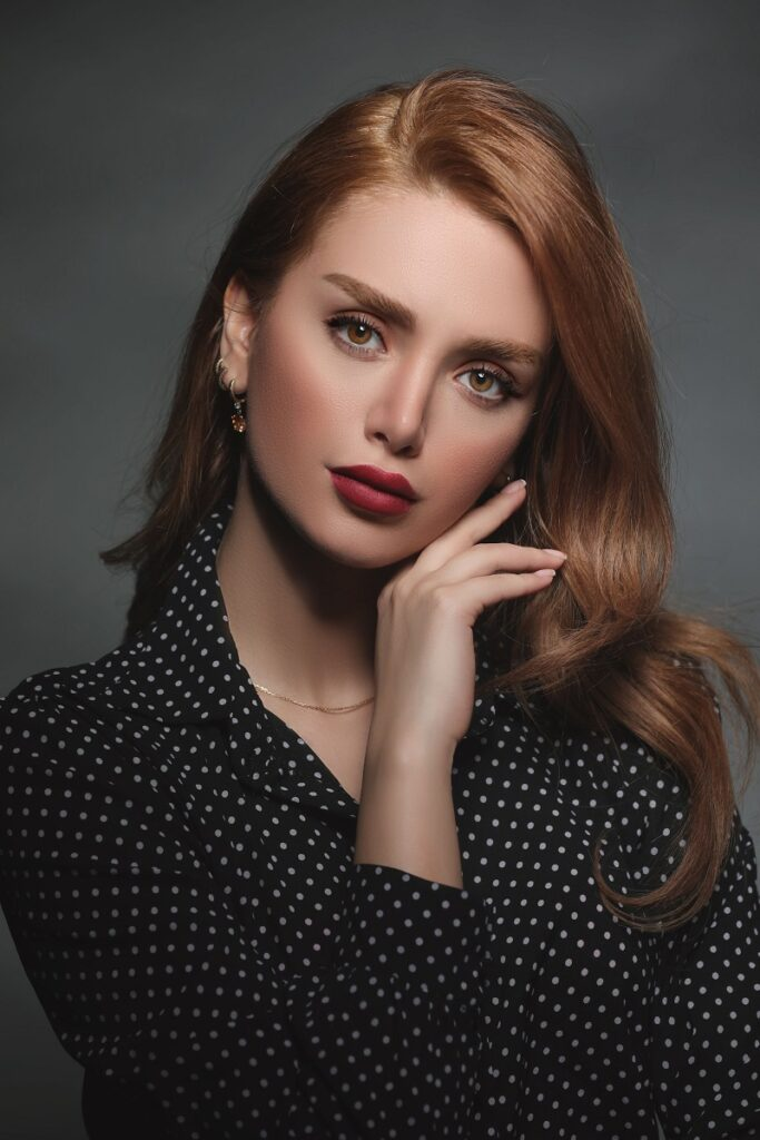 A portrait photo of a woman in black and white polka dot shirt