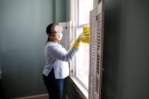 A woman cleaning windows wearing mask and goggles